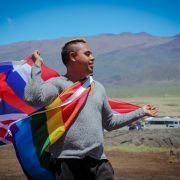 A young man in a gray sweatshirt holds a LGBTQ+ rainbow flag along with the flag of Hawaii.
