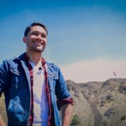 Kaniela Ing. A portrait of a smiling man wearing a denim jacket