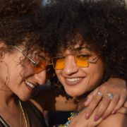 Two women wearing yellow sunglasses with big loosely curled afros hug