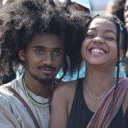 A young Black man with a giant afro stands behind a young Black girl with braids who is laughing