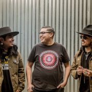 Yerena, stands between two fellow Chicano/Native artists, Josue Rivas and Cempoalli Twenny. Rivas and Twenny are wearing black leather cowboy hats and brown canvas bomber jackets.