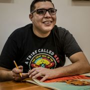 "A smiling Chicano/Native artist in black glasses, wearing a ""Tribe Called Red"" t-shirt smiles while sitting at his deask"