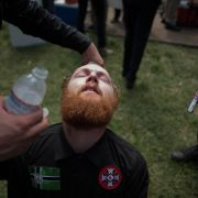 A red-bearded White man wearing a shirt with a Ku Klux Klan cross has water poured over his closed eyes, a treatment for pepper spray.
