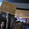 "Asian woman holds sign that reads, ""Deport racism."""