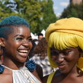 A Black women with a short turquoise natural and glitter on her face laughs with another Black woman wearing a yellow wig and a yellow hat