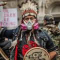 Man in white feather headdress wearing a pink and gray gas mask and denim jacket beats on a drum
