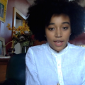 Black woman with curly hair and white button-down shirt sits in large room with red walls and yellow flowers