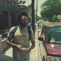 "Donald Glover in shirt reading ""keep on keeping on"" while walking on street"