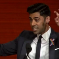 Hasan Minhaj with black suit and white shirt, rainbow flag pin, red background