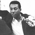 Kwame Ture in black-and-white, seated in front of microphone