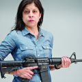 A woman in a denim shirt holds an AR-15 semiautomatic rifle