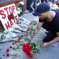 A man in New York City lays 50 red roses on an outdoor altar to commemorate the Pulse victims who died.