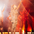 Beyoncé and dancers raise their fists on stage, surrounded by fire and water