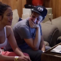 Blurry image of Jennifer Lopez in white tank top and Lin-Manuel Miranda in black cap and grey t-shirt