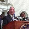 Blurry image of John Bel Edwards surrounded by officials at brown podium with white background
