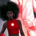 Riri Williams in red shirt with glowing red orb in center of body