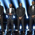 Four Black men in black tuxedos on a black stage with blue lights behind them