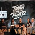 """panelists seated in front of black background with white text reading """"Truth to Power"""""""