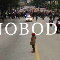 Black boy stands in middle of roads, police officers in the distance