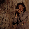 Barbara O. Jones in multicolored dress against brown tree trunk