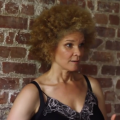 Black woman with blonde Afro wearing a black slip