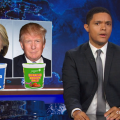 """Black man sits at desk, picture of Donald Trump and Hillary Clinton is behind him; Clinton has container of """"Vanilla"""" yogurt, Trump has picture of """"Siracha Baboon Anus"""" yogurt"""