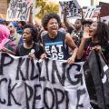 Black protestors march in the streets of Harlem