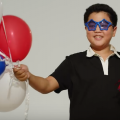Asian teen with black hair, blue sparkling sunglasses and black polo with white collar, holding red, white and blue balloons and noisemaker