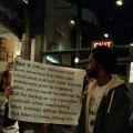 people holding brown and white signs with black text under dimily lit scaffolding against black sky