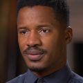 Nate Parker in navy button-down against brown background