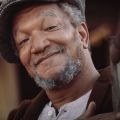 Redd Foxx in brown jacket, white shirt and grey cap against brown background