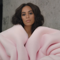 Solange Knowles in big pink coat against brown background