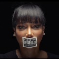 "Michele with black-and-white ""parental advisory"" sticker on mouth against black background"