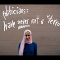 Woman in blue shirt and pink hijab against brown brick wall with white lettering