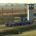 Men in blue prison jumpsuits walking on green and brown field against brown fence and white-and-brown patrol tower