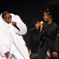 Black man in white coat and black sunglasses next to Black woman in black blouse and pants against dark performance background