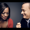 Black woman in red dress looking down next to White man in black jacket looking left against grey background