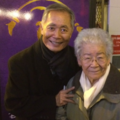 George Takei, wearing a black jacket, stands next to a Japanese-American grandmother wearing a brown jacket and white scarf.