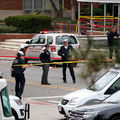 White policemen in navy uniforms and hats and helmets by a black, white and red police cruiser, near yellow and black crime scene tape against brown buildings