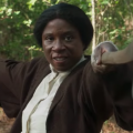 Black woman holding brown rifle and brown-and-grey axe while wearing brown coat and white shirt against brown and green foliage