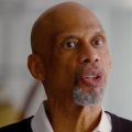 Black man in black sweater and white collared shirt against blurry grey background