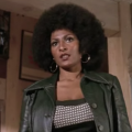 Black woman with black afro in black leather jacket and grey shirt against brown wall