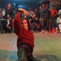 Brown dancer in red shirt and black leather pants on brown dancefloor surrounded by Black and Brown individuals
