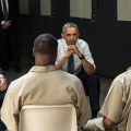 White man with navy shirt and blue jeans next to Black man in white shirt and navy tie and navy pants in front of men in brown prison uniforms, all against grey floor and white wall with blue doors