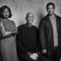 Greyscale photo of Black woman in dress standing next to Black man in sweater and collared shirt and pants seated next to Black man in blazer and shirt and pants