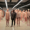 Kanye West stands in front of a large group of White models wearing his flesh-colored Yeezy collection of leggings, shirts, body suits and other garments.