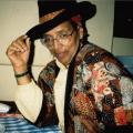 A seated Audre Lorde beams while wearing a black hat and a multicolored patchwork jacket