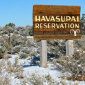 """Brown sign with yellow text reading """"Havasupai Reservation"""" on two light brown poles against white snow-covered desert"""