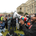 Black man speaks into megaphone, protestors surround him