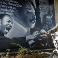 Two young Black girls ride by a black and white Martin Luther King mural in Miami